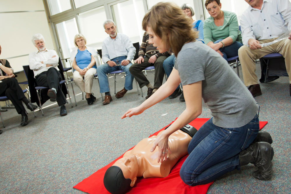A woman performing the first aid and CPR on a manikin in a training room for students